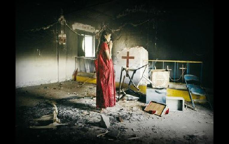 Donna in preghiera in chiesa distrutta dai terroristi in medio oriente